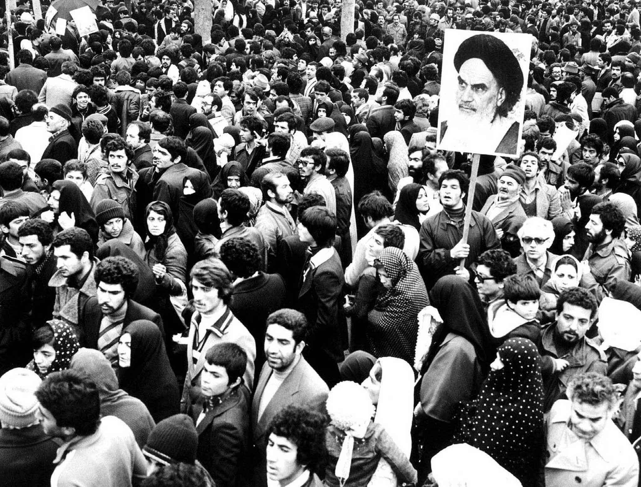 IRANIANS HOLD PICTURE OF KHOMEINI DURING THE REVOLUTION.